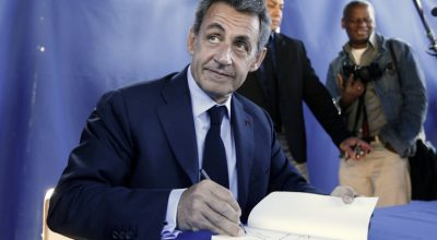 """Former French president and President of France's right-wing Les Republicains (LR) Nicolas Sarkozy signs his book """"La France Pour La Vie"""" or """"France for Life"""" before a meeting in Nice on April 26, 2016, southeastern France.  / AFP PHOTO / VALERY HACHE"""