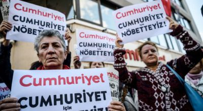 """Protesters hold a sign reading """"We are here for Cumhuriyet"""" during a protest in front of opposition Cumhuriyet newspaper in Istanbul on October 31, 2016 after a police operation at the daily's headquarters.  Turkish police detained the editor-in-chief of the opposition newspaper Cumhuriyet, state media reported. According to CNN Turk, 13 arrest warrants were issued for journalists and executives from the daily. The Istanbul prosecutor said an investigation had been launched into allegations the paper's output was """"legitimising"""" the July 15 failed coup. / AFP PHOTO / OZAN KOSE"""