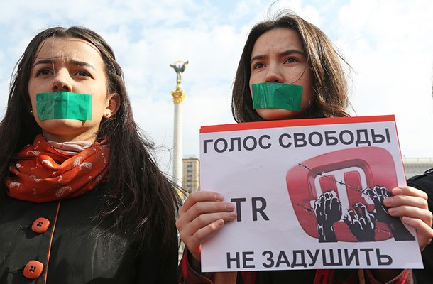 """Activists stood with their mouths taped holding posters which read """"the voice of freedom cannot be silence"""" during a rally to support ATR TV channel in Kyiv's Independence Square on March 28."""