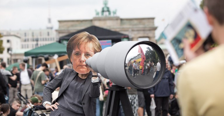 A demonstrator wearing a mask depicting German Chancellor Angela Merkel looks through a mock telescope during a demonstration against governmental surveillance on August 30, 2014 in Berlin.  AFP PHOTO / DPA/ JÖRG CARSTENSEN   GERMANY OUT