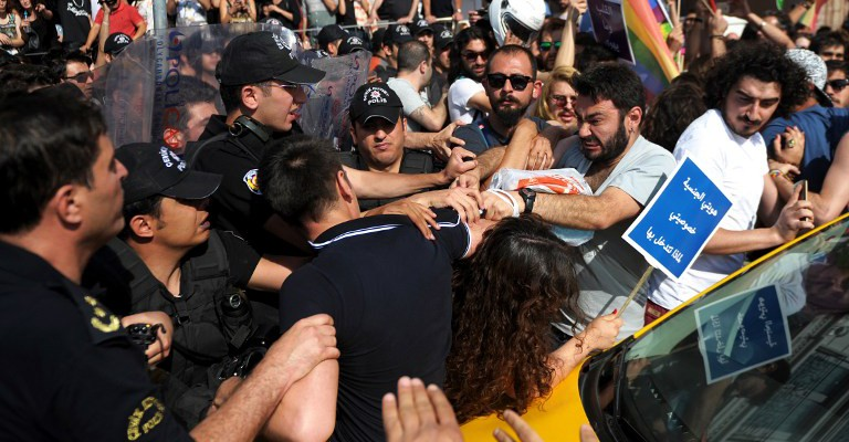 """Turkish riot police officers clash with protesters on June 28 ,2015 near the Taksim square in Istanbul. Riot police in Istanbul used teargas and water cannon to disperse thousands of participants of the Gay Pride parade in the Turkish city. Police took action against the crowd when demonstrators began shouting slogans accusing the social conservative President Recep Tayyip Erdogan of """"fascism"""". AFP PHOTO/OZAN KOSE"""