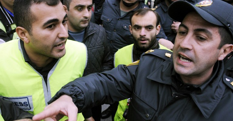 A police officer argues with a journalist wearing a reporter's identification yellow vest during a rally to demand the dissolution of parliament and the resignation of President Ilham Aliyev on the Fountains Square in central Baku, on November 17, 2012. Police broke up today an unauthorised pro-democracy protest by around 100 opposition activists in central Baku, detaining dozens and beating up several journalists. AFP PHOTO/ TOFIK BABAYEV