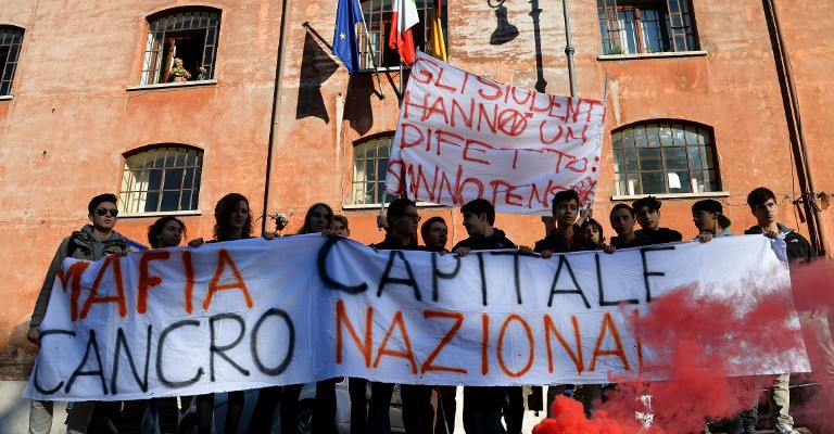 """Students hold a banner reading """"Mafia capital, National cancer"""" in downtown Rome on December 12, 2014 during an eight-hour-strike called by the CGIL and UIL unions to protest against measures contained in the 2015 budget bill and against Italian Prime Minister Matteo Renzi's government controversial Jobs Act, which they say threatens employment and workers' rights.      AFP PHOTO / ALBERTO PIZZOLI"""