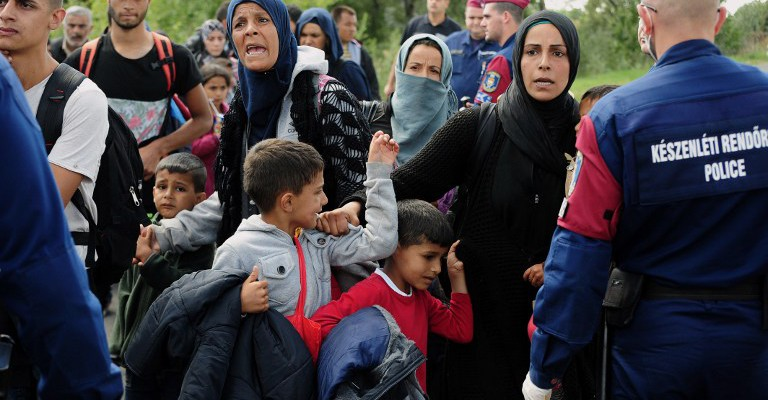 Police officers stop a group of migrants after a migrant crowd broke out of at collection point near Roszke village at the Hungarian-Serbian border on September 9, 2015. Some 400-500 migrants on Wednesday broke through police lines in Hungary near the main crossing point from Serbia.  AFP PHOTO / CSABA SEGESVARI