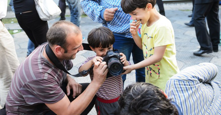 A photographer lets a kid use his camera at a registration center in Brezice on September 19, 2015. Hundreds of migrants gathered on Croatia's main border crossings with Slovenia today, seeking transit through Slovenian territory in their bid to travel to northern Europe, AFP reporters and local media said.  AFP PHOTO / JURE MAKOVEC