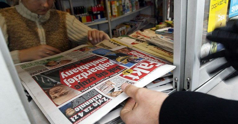 """A man buys a copy of the new Polish daily """"Fakt"""" published by the German media group, Axel Springer Poland in downtown Warsaw, 23 October 2003. """"Fakt"""" aims to be the equivalent of Germany's """"Bild"""" and will publish 700,000 copies daily, the highest figure of all the news dailies published in Poland.   AFP PHOTO JANEK SKARZYNSKI / AFP / JANEK SKARZYNSKI"""