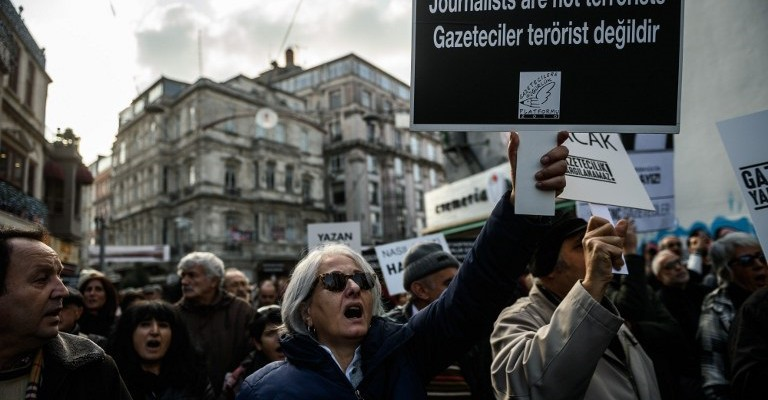 "Journalists and Turkish intellectuals shout slogans during a demonstration on December 26, 2015 in Istanbul, following the arrest of Cumhuriyet newspaper's Editor in Chief last month.  A court in Istanbul charged two journalists from the opposition Cumhuriyet newspaper with spying after they alleged Turkey's secret services had sent arms to Islamist rebels in Syria, Turkish media reported. Editor-in-chief Can Dundar and Erdem Gul, the paper's Ankara bureau chief, are accused of spying and ""divulging state secrets"". Both men were placed in pre-trial detention.  / AFP / OZAN KOSE"