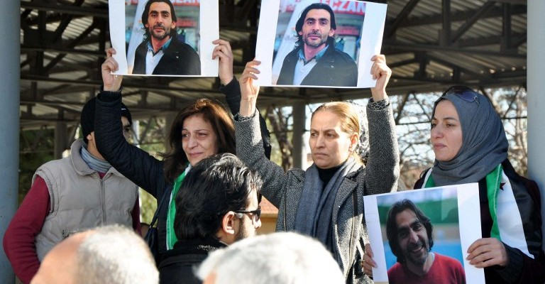 """Women hold pictures of film maker Naji Jerf, who was killed on December 27, during his funeral in Gaziantep on December 28, 2015.  Naji Jerf, a Syrian activist who produced documentaries hostile to the Islamic State group, was assassinated in Turkey on December 27, according to the group with which he worked, """"Raqa is Being Slaughtered Silently"""". RBSS is a group of citizen journalists who work to expose human rights abuses in Raqa, the northeastern city that IS uses as its de facto capital in Syria / AFP / STR / Turkey OUT"""