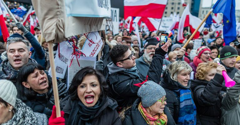 People attend a protest against a new media law in the center of Warsaw on January 9, 2016.  Since returning to power in October, Poland's Law and Justice (PiS) party has taken several controversial step which critics have denounced as undermining the independence of both the media and the judiciary. / AFP / WOJTEK RADWANSKI
