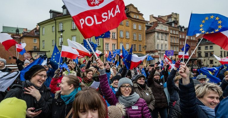 """People wave European and Polish flags and sing the European anthem """"Ode to Joy"""" as they take part in a flash mob to protest against a new media law in the center of Warsaw on January 9, 2016.  Since returning to power in October, Poland's Law and Justice (PiS) party has taken several controversial step which critics have denounced as undermining the independence of both the media and the judiciary. / AFP / AFP PHOTO / WOJTEK RADWANSKI"""