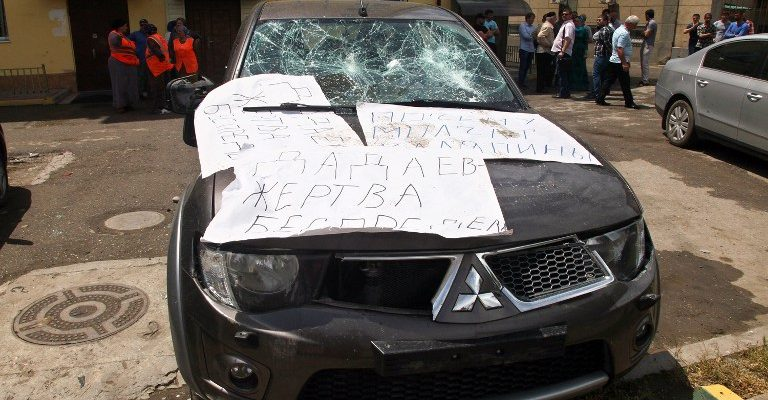 "The damaged car covered by posters reading ""Dadayev is a victim of outrage!"" referring to Zaur Dadayev, one of the two Chechens officially accused of the murder of  Russian opposition activist  Boris Nemtsov, is parked at the office of the Committee Against Torture in Grozny on June 3, 2015. One of the last rights groups active in Russia's Chechnya region said today that masked attackers were ransacking its offices as crowds of pro-government demonstrators stood outside. The group of young men broke down the door of the office and ""started smashing everything"", forcing staff to escape through windows, the prominent rights group Committee Against Torture said on its Twitter account. AFP PHOTO / STR / AFP / STR"