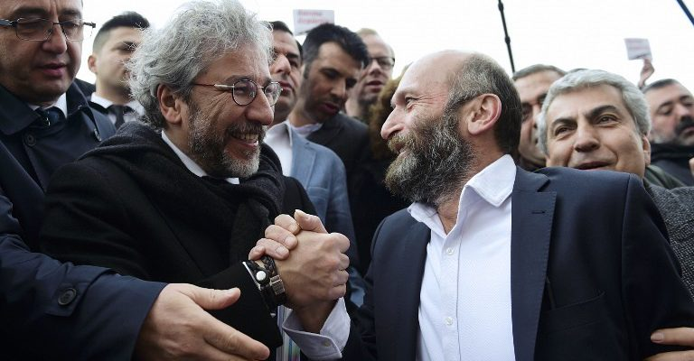 Turkish daily Cumhuriyet's editor-in-chief Can Dundar (L) and Ankara editor Erdem Gul (R) hold hands as they arrive at the Istanbul courthouse before his trial on March 25, 2016. Two top Turkish journalists are going on trial, accused of espionage and other serious crimes and facing possible life in prison over a story about Turkey's role in the Syrian conflict that infuriated President Recep Tayyip Erdogan. / AFP / BULENT KILIC