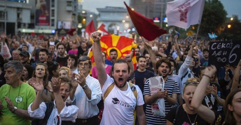 Protesters shout slogans in front of the Parliament building  in Skopje on April 18, 2016, during a protest against the president's shock decision to halt probes into more than 50 public figures embroiled in a wire-tapping scandal.  The country has been politically gridlocked for two years but the crisis rose a notch on April 12 when President Gjorge Ivanov halted a probe into more than 50 public figures suspected of involvement in corruption and a wire-tapping scandal. The move triggered street protests against Ivanov and the ruling party's leader, Nikola Gruevski. Fresh demonstrations on Monday drew several thousand, mostly young people who demanded Ivanov's resignation. / AFP PHOTO / Robert ATANASOVSKI