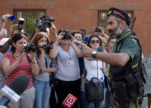 An armed man speaks to the press after pro-opposition gunmen locked in a week-long hostage standoff with Armenian authorities released the final four police officers held captive in Yerevan on July 23, 2016.    A group of supporters of jailed opposition leader Zhirair Sefilyan stormed a police building in the capital Yerevan on July 17, 2016, killing one officer, taking several more hostage and seizing a cache of weapons.  / AFP PHOTO / KAREN MINASYAN
