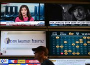 A man walks past video screens displaying TV channels in Athens on August 30, 2016.  Greece  launched a multi-million euro auction for four private TV licences, a process originally due two decades ago and now marked by political infighting. Eight groups are vying for the four 10-year nationwide licences, with opening bids starting at three million euros ($3.4 million).Their representatives will be locked up in an office building with no outside communication until the process is complete, a move prompting angry protests from TV managers.  / AFP PHOTO / LOUISA GOULIAMAKI