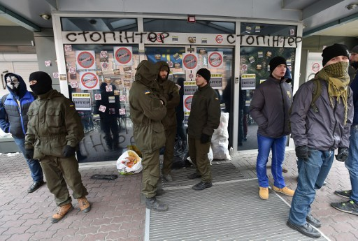 """A group of activists block the entrance of the main office of the Ukrainian TV Channel """"Inter"""" in Kiev on February 25, 2016.  Activists, mostly members of """"Azov"""" civilian corps, demand to stop broadcasting of """"Inter"""" and accuse the channel of being under the """"Kremlin censorship"""" and distributing pro-Russian propaganda, which misrepresents the events in Ukraine.  / AFP PHOTO / GENYA SAVILOV"""