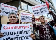 "Protesters hold a sign reading ""We are here for Cumhuriyet"" during a protest in front of opposition Cumhuriyet newspaper in Istanbul on October 31, 2016 after a police operation at the daily's headquarters.  Turkish police detained the editor-in-chief of the opposition newspaper Cumhuriyet, state media reported. According to CNN Turk, 13 arrest warrants were issued for journalists and executives from the daily. The Istanbul prosecutor said an investigation had been launched into allegations the paper's output was ""legitimising"" the July 15 failed coup. / AFP PHOTO / OZAN KOSE"