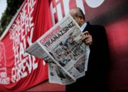 "A man reads a copy of the latest edition of the Turkish daily newspaper ""Cumhuriyet""  during a demonstration outside the newspaper's headquarters in Istanbul on November 2,2016. Turkish police on November 1, 2016, detained the editor-in-chief of the newspaper Cumhuriyet -- a thorn in the side of President Recep Tayyip Erdogan -- as Ankara widens a crackdown on opposition media. The Cumhuriyet, which had published revelations embarrassing for the government, said at least a dozen journalists and executives were detained in early morning raids. The raids came after authorities fired more than 10,000 civil servants at the weekend and closed 15 pro-Kurdish and other media outlets, the latest purge since July's failed military coup aimed at ousting Erdogan. / AFP PHOTO / YASIN AKGUL"